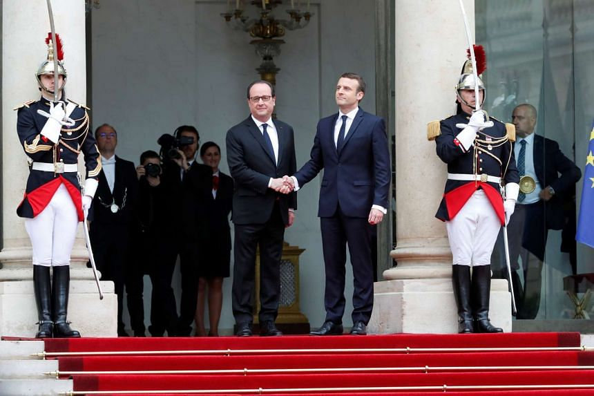 Outgoing French President Francois Hollande cordially greeting President-elect Emmanuel Macron ahead of the handover ceremony at the Elysee Palace in Paris, France. PHOTO: REUTERS