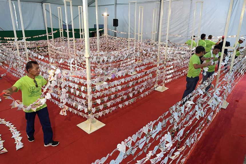 Volunteers for charity Jamiyah Singapore creating a chain of 8,525 paper hearts yesterday in a bid to set a Guinness World Record for the Longest Chain of Paper Hearts. The chain was assessed at a carnival in celebration of the charity's 85th anniver