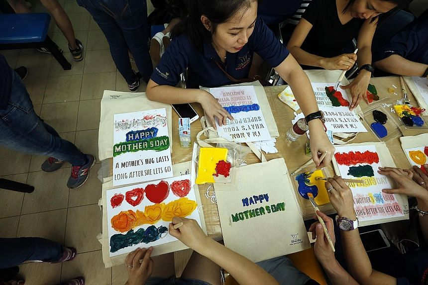Marina Bay Sands (MBS) staff painting tote bags for underprivileged mothers at the Singapore Association for the Deaf (SADeaf) yesterday, ahead of Mother's Day today. MBS has partnered SADeaf since 2013. Ms Grace Phua with her parents Angela Lee and