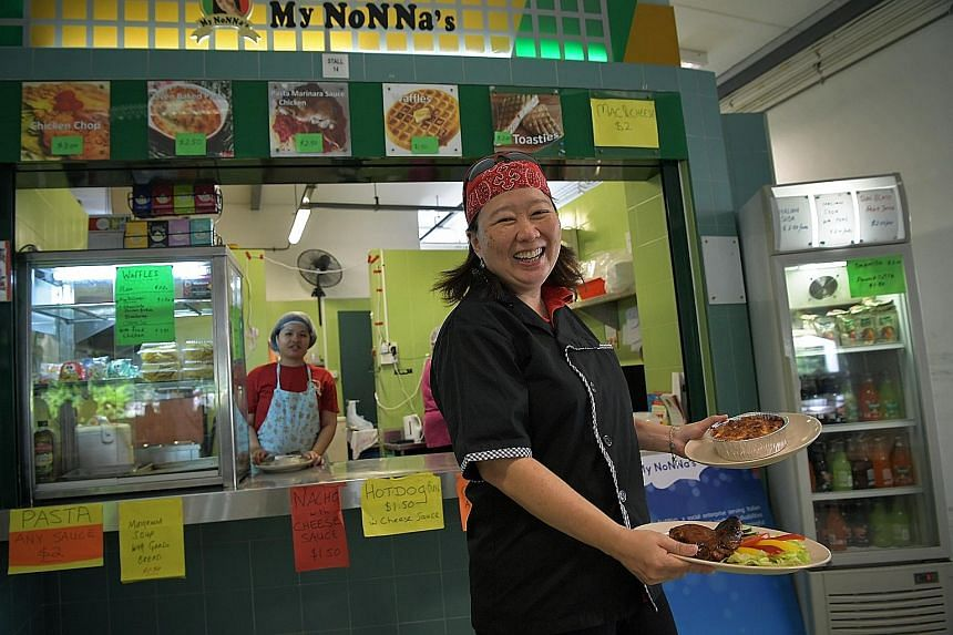The founder of My Nonna's, Ms Geraldine Tan, outside her stall in the Raffles Institution canteen. Stall assistant Goh Wei Ting (at the counter) says she enjoys cooking for the students.