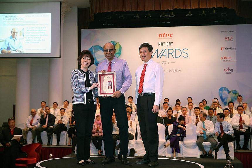 Mr Tharman Shanmugaratnam receiving the Medal of Honour from NTUC president Mary Liew and secretary-general Chan Chun Sing.