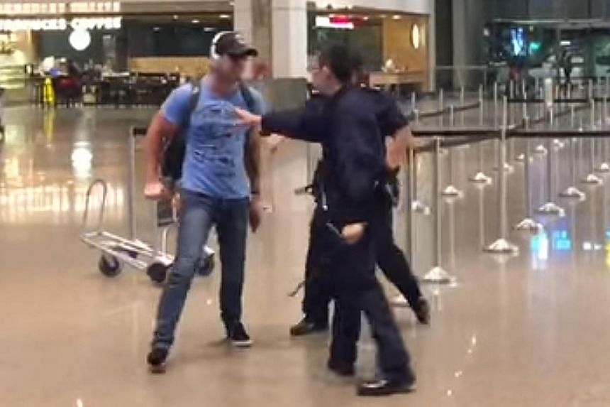 A screenshot from one of two videos showing a man, believed to be the accused, tussling with police at Changi Airport last month.