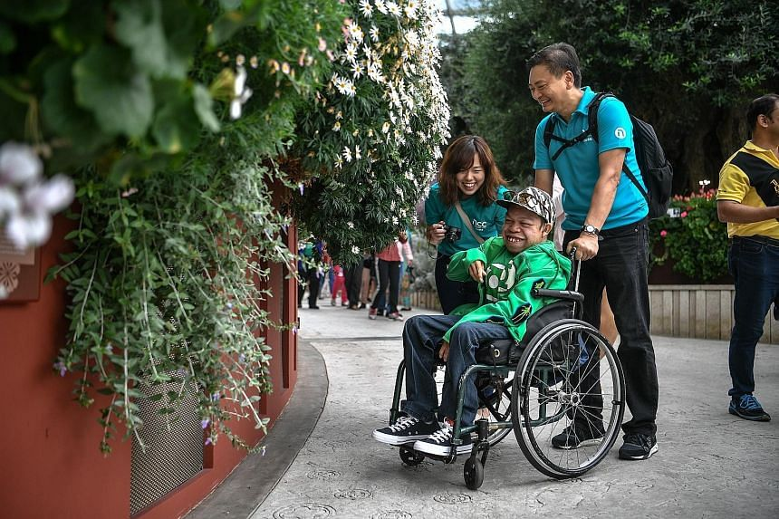 Mr Muhammad Idham Fayumi Ruslan with Awwa volunteers Michael Goh and Sara Ashley Sim at Gardens by the Bay last Sunday. Two to three times a week, Awwa staff visit Mr Idham at his home for physiotherapy.