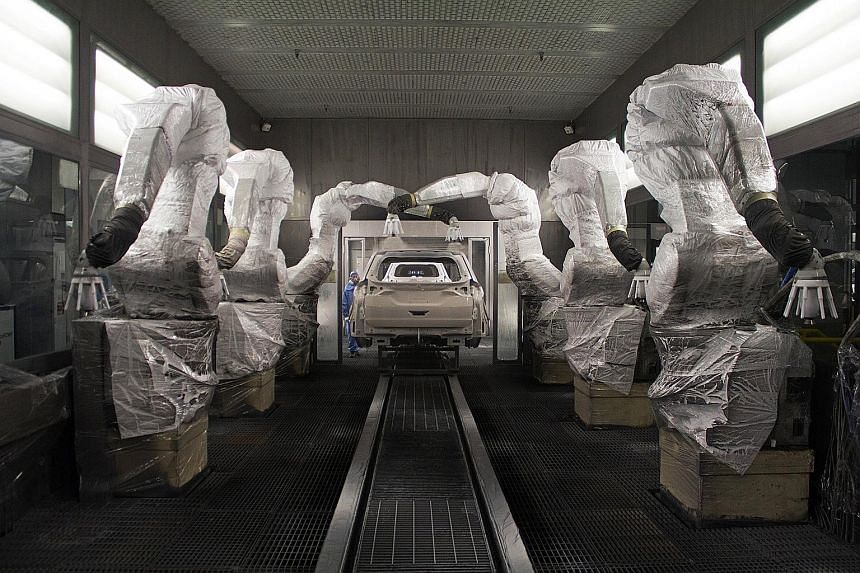 Robots covered in multiple layers of plastic apply primer to vehicle frames at Ford's Hangzhou plant. Robots perform tasks like welding and painting in exactly the same way every time, improving quality control.