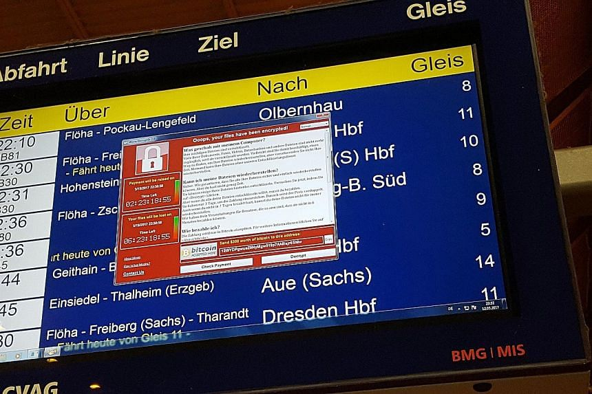 Above: A window announcing the encryption of data including a requirement to pay appears on an electronic timetable display at the railway station in Chemnitz, eastern Germany, last Friday. Left: The website of the NHS: East and North Hertfordshire n