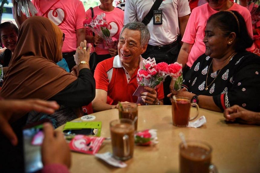 Prime Minister Lee Hsien Loong gives out flowers to mothers at Hougang Avenue 8 on Sunday (May 14).