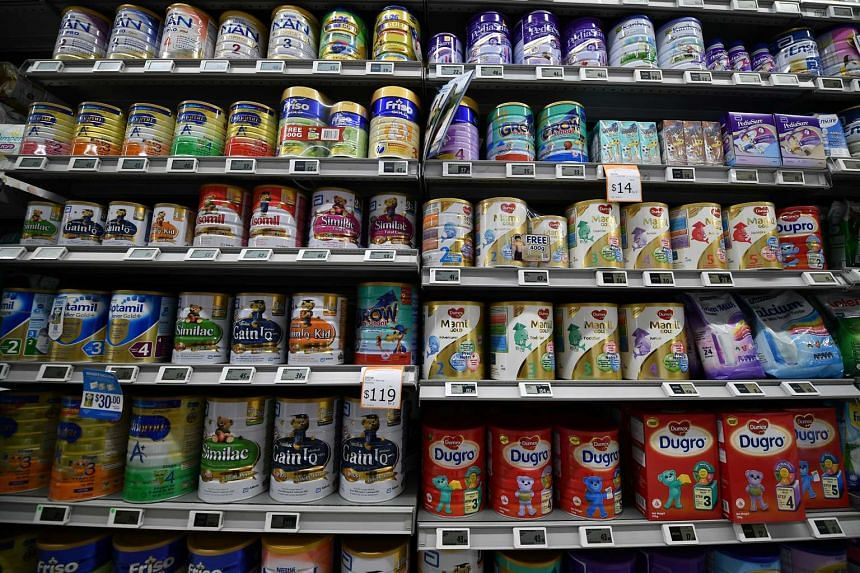 Tins of formula milk powder displayed on shelves at a supermarket.