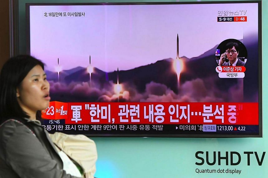 A woman walks past a television screen showing file footage of a North Korean missile launch, at a railway station in Seoul on March 22, 2017.
