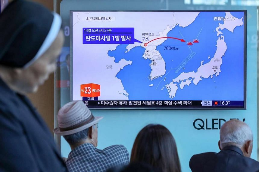 People watch a news report on North Korea firing a ballistic missile, at a railway station in Seoul.