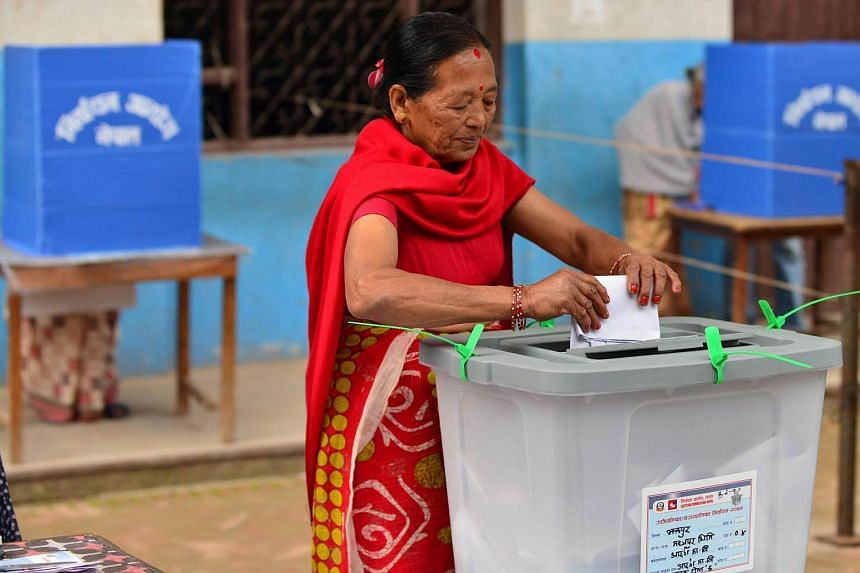 A woman casts her vote at a polling station in Thimi, on the outskirts of Kathmandu, on Sunday (May 14).