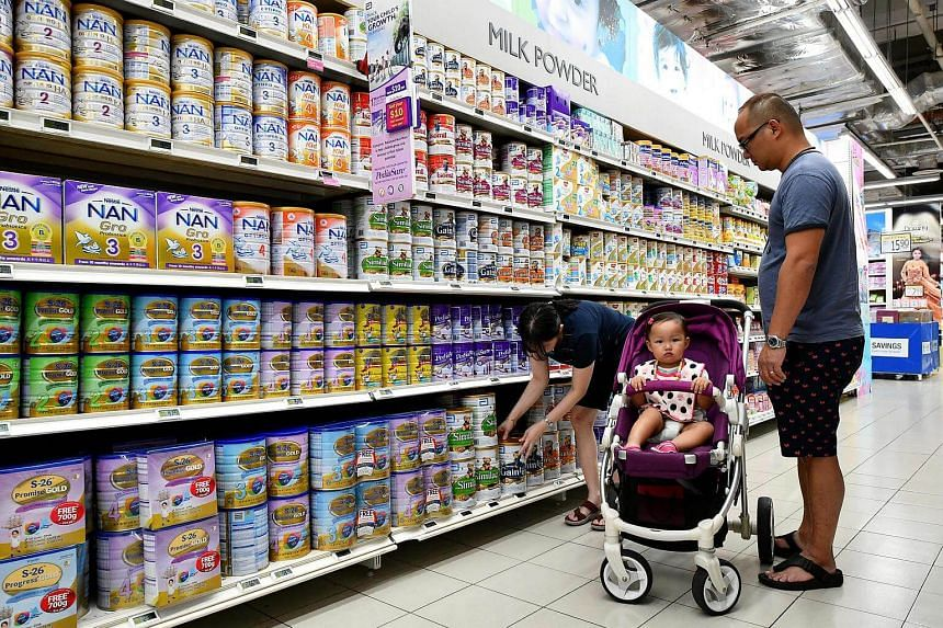 Customers looking for milk powder among rows of infant milk powder tins in FairPrice Xtra supermarket at Nex.