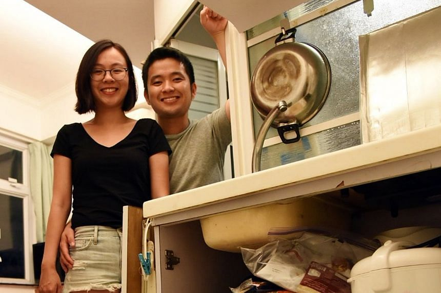 Singaporean couple Lim Wei Wen and Tan Yan Han in their Hong Kong flat which has room for just a bed and a tiny kitchen. The bed frame doubles as an ironing board and dining table.