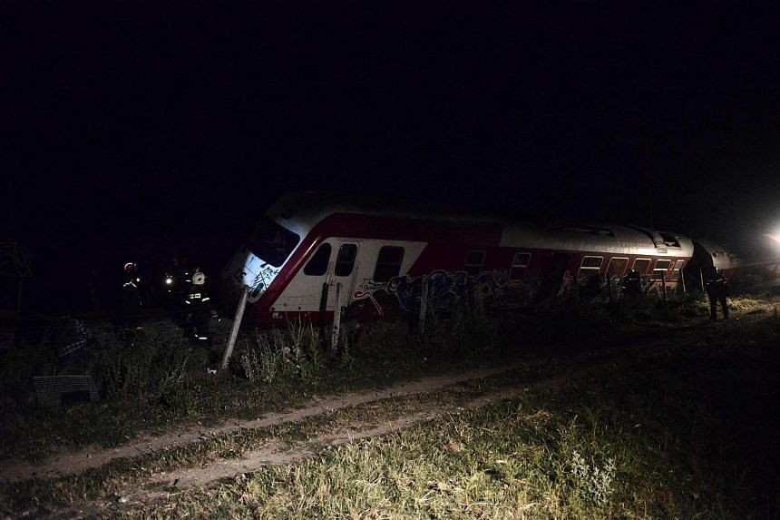 Firefighters stand next to derailed wagons from a train near the village of Adendro some 40 km west of Thessaloniki, Northern Greece.
