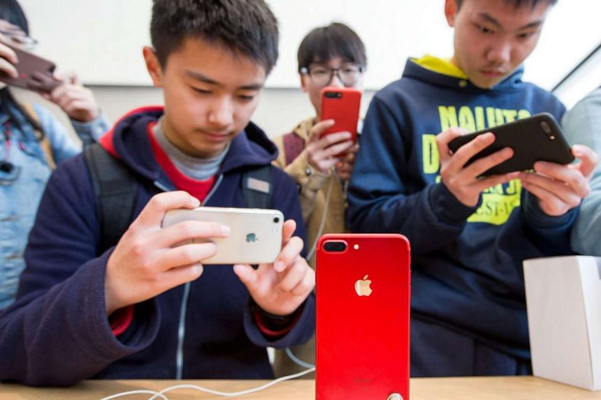 Brandishing their iPhones, customers at an Apple Store in Nanjing, China, take photographs of a new red iPhone 7 Plus. Apple has released a new photography guide to help users maximise the iPhone camera's effectiveness. PHOTO: REUTERS