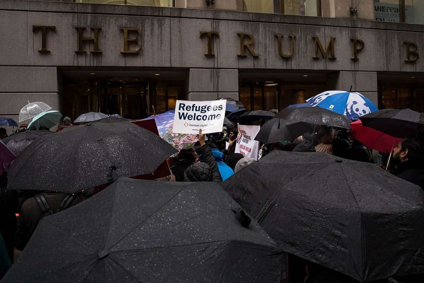 Protesters rally in front of the Trump Building to protest against the Trump administration's proposed travel ban and refugee policies, on March 28, 2017.