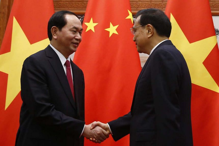 Chinese Premier Li Keqiang (right) shakes hands with Vietnamese President Tran Dai Quang (left) at the Great Hall of the People in Beijing, China on May 12, 2017.