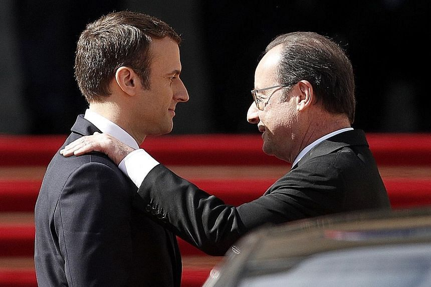 French outgoing President Francois Hollande (right) being escorted by his successor, Mr Emmanuel Macron, as he leaves the Elysee presidential Palace at the end of their handover ceremony yesterday.