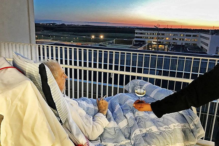 Mr Carsten Hansen watching the sunset from his hospital bed in Denmark as he enjoys a puff and a glass of white wine.