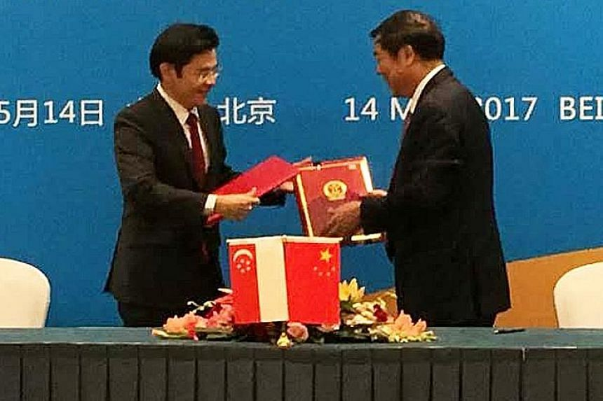 Mr Lawrence Wong (far left) with Mr He Lifeng, head of China's National Development and Reform Commission, at the MOU signing yesterday.
