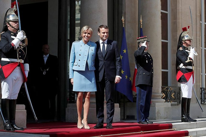 French President Emmanuel Macron, 39, and his wife, Ms Brigitte Trogneux, 64, on the steps of the Elysee Palace in Paris yesterday after the inauguration ceremony. The centrist newcomer stands outside any traditional political grouping and is a Europ