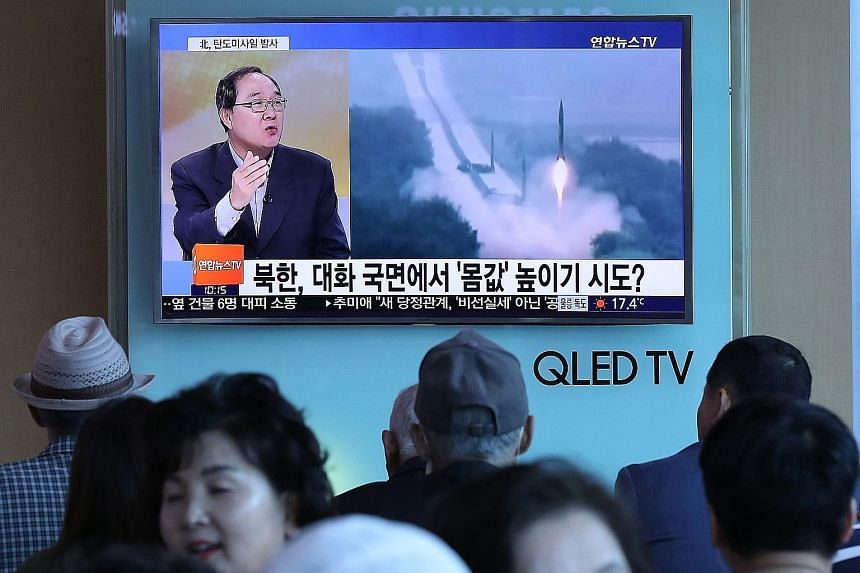 A news programme with file footage of a North Korean missile launch shown yesterday at a railway station in Seoul. The North fired a missile that landed in waters between North Korea and Japan yesterday.