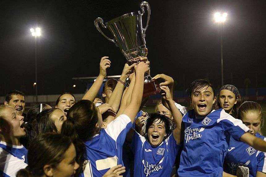 Left: The AEM Lleida girls' amateur team celebrating their league title triumph last month, as they emerged tops in a junior regional boys' league in Spain. Far left: AEM's top scorer Andrea Gomez leaping high to head the ball over the boys. She scor