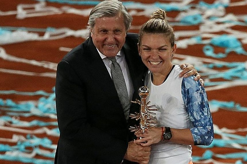 Simona Halep posing with her Fed Cup coach Ilie Nastase after winning her second straight Madrid Open title. Nastase is banned from the French Open and Wimbledon after a series of foul-mouthed rants last month.