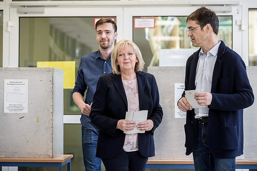 Above: Mr Armin Laschet of the CDU, with his wife Susanne, casting his ballot at a polling station in Aachen, western Germany, yesterday. Left: The SPD's Ms Hannelore Kraft, with her husband Udo and son Jan, about to cast her ballot in Muelheim an de
