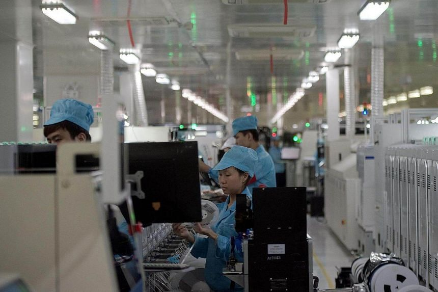 Factory employees work at the main factory of Chinese smartphone maker Oppo in Dongguan.