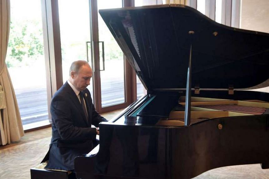 Russian President Vladimir Putin plays the piano before meeting Chinese leader Xi Jinping in Beijing on May 14, 2017.