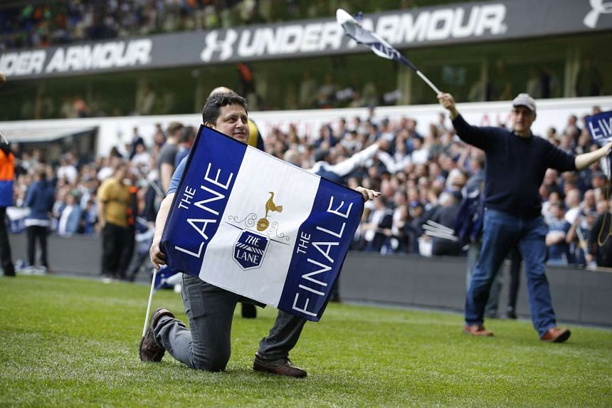 Tottenham fans celebrate on the pitch after the match.