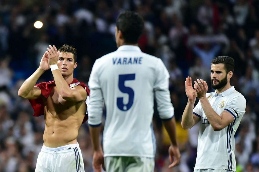 Cristiano Ronaldo (L) applauds after the match against Sevilla on May 14, 2017.