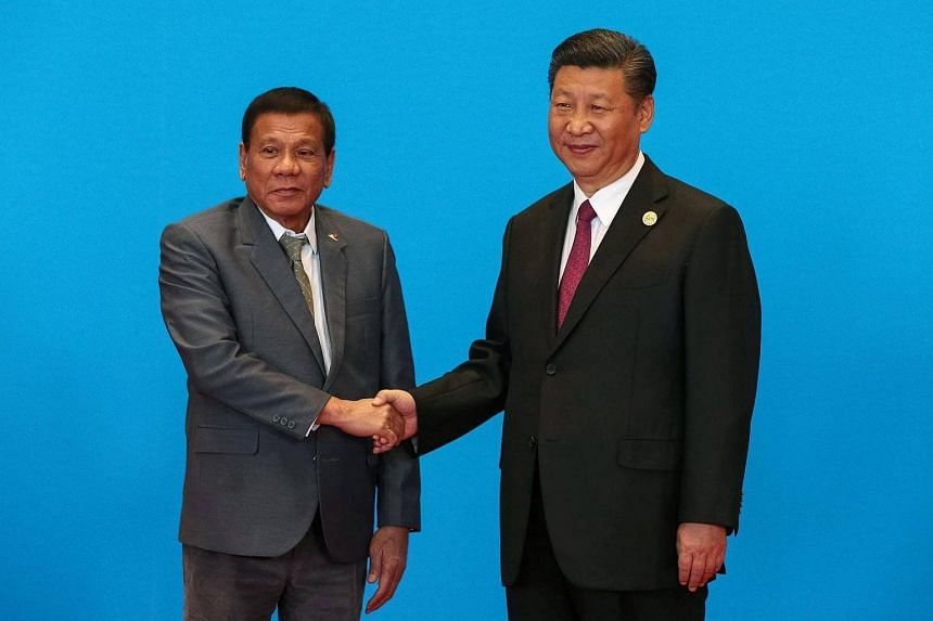 China's President Xi Jinping (right) shakes hands with his Philippine counterpart Rodrigo Duterte in Beijing on May 15, 2017.