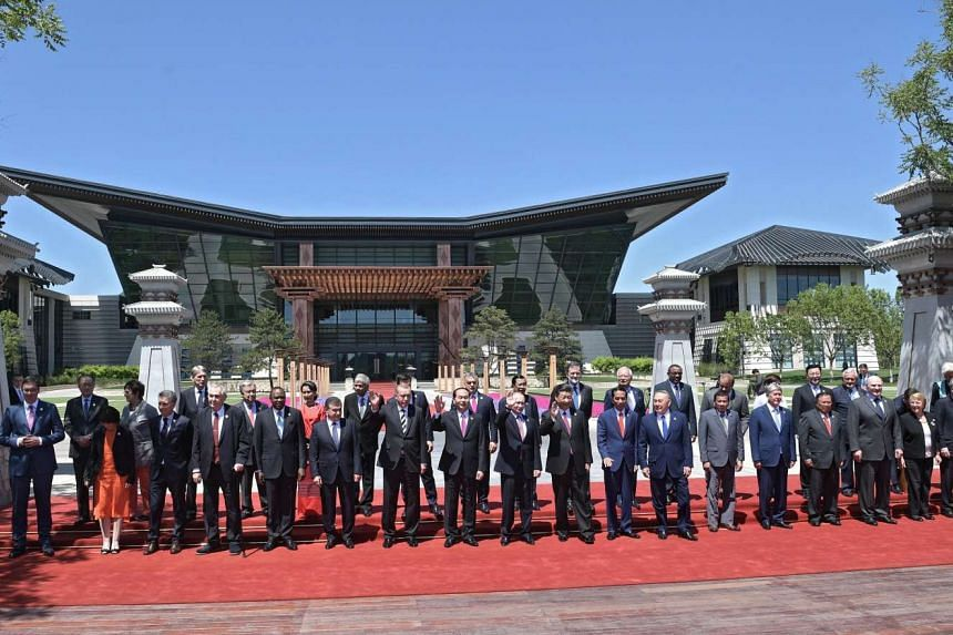 Leaders attending the Belt and Road Forum wave as they pose for a group photo at the International Conference Centre at Yanqi Lake, Beijing, China, on May 15, 2017.
