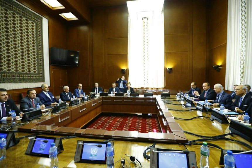 UN Special Envoy for Syria Staffan de Mistura (second right) and Syrian government negotiator Bashar Ja'afari (third left) and their delegations attend a meeting during talks in Geneva on May 16, 2017.