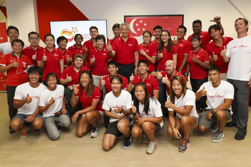 Prime Minister Lee Hsien Loong shares a photo moment with Team Singapore athletes and officials at the SSI Athlete Service Centre at the end of his visit to the Singapore Sports Institute.
