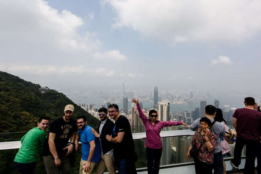Tourists posing for photos at the viewing deck of Victoria Peak in Hong Kong on April 4, 2017.