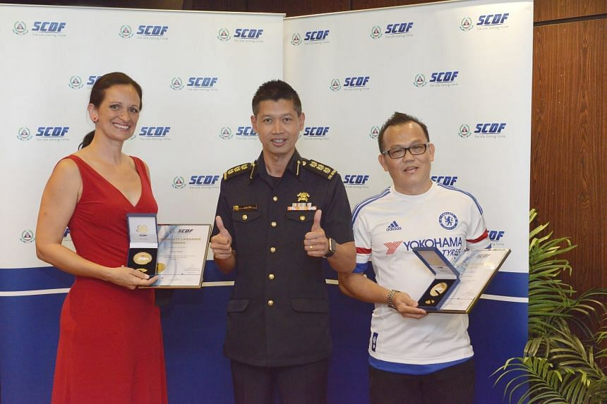 Colonel Alan Toh, Commander 2nd SCDF Division (centre), and award recipients Ms Silvia Hajas (left), 47, housewife, and Mr Tan Kian Choon (right), 53, self-employed, posing with the SCDF Lifesaver Award.