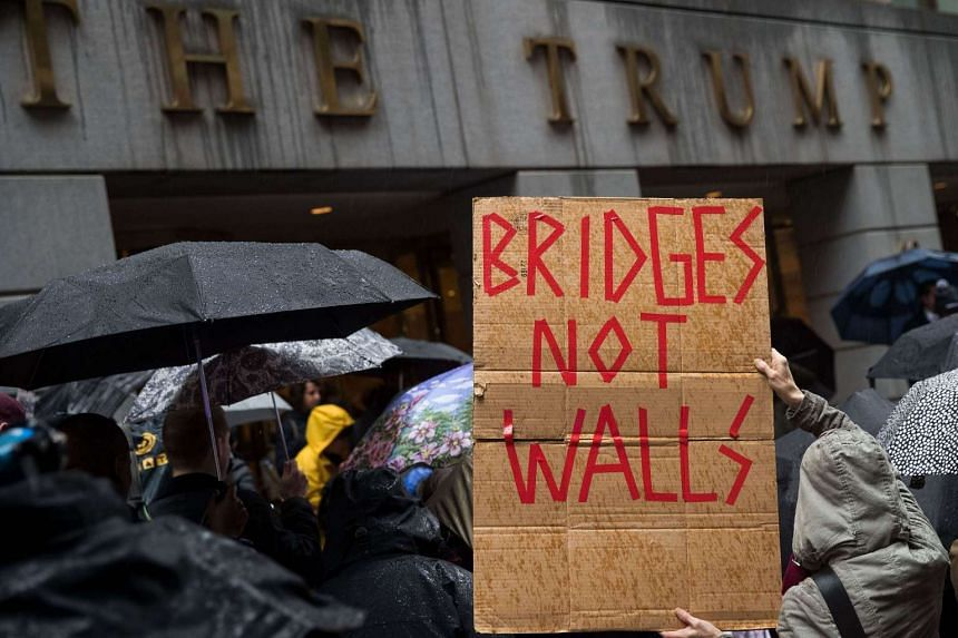 Protesters rally in front of the Trump Building on Wall Street during a protest against the Trump administration's proposed travel ban and refugee policies, in New York City, on March 28, 2017.