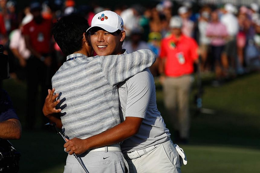 Kim Si Woo celebrates with his father on the 18th green after winning the Players Championship. The 21-year-old is the youngest winner of the PGA Tour's flagship event.