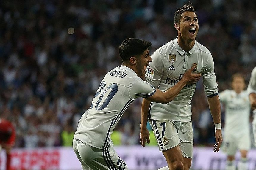 Real Madrid's Marco Asensio (left) congratulates Cristiano Ronaldo after Zinedine Zidane's side scored their third goal in the 4-1 win against Sevilla. The Portuguese striker scored his 400th and 401st goals for Real Madrid in the course of the victo
