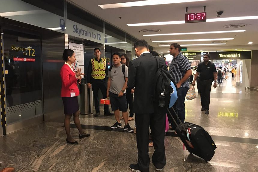 Airport staff at Changi Terminal 1 telling passengers that the Skytrain to Terminal 2 is not in operation, and asking them to go to the Terminal 3 assembly area for further instructions, on May 16, 2017.