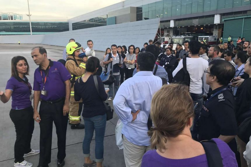 Airport staff giving instructions to people gathered on the tarmac, after the departure hall in Changi Airport Terminal 2 was evacuated, on May 16, 2017.