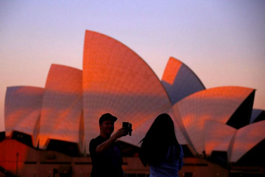 Tourists take photographs of each other in front of the Sydney Opera House at sunset in Sydney.