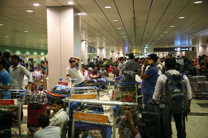 Stranded passengers diverted from T2 at T3 waiting for updates on their flights.