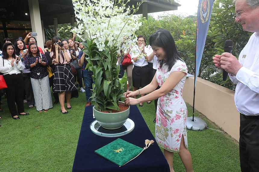 Mrs Lai Chiew Yen - the wife of Singapore's Chief of Navy, Rear-Admiral Lai Chung Han - placing a nameplate into a pot of orchids at the Botanic Gardens yesterday. The orchid-naming ceremony was held before an international gathering of navy wives. T