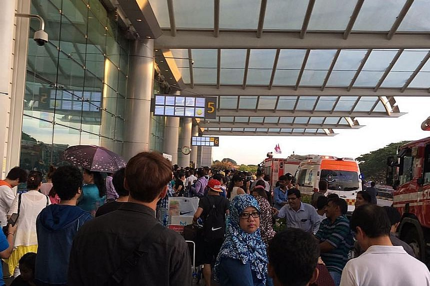 Smoke at Changi Airport Terminal 2 yesterday. Thousands of departing passengers ended up being delayed, some for more than three hours, following the fire. Passengers waiting outside Changi Airport Terminal 2. While some complained about the long wai