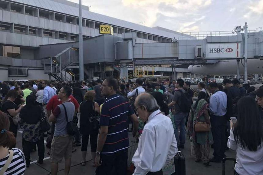 People standing on the tarmac after the departure hall in Changi Airport Terminal 2 was evacuated, on May 16, 2017.