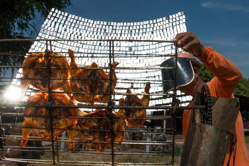 Food vendor Sila Sutharat turning the grates on a cart loaded with chicken as he cooks the white meat with rays of sun reflected on an oversized mirror panel on his property in Petchaburi province, south of Bangkok.