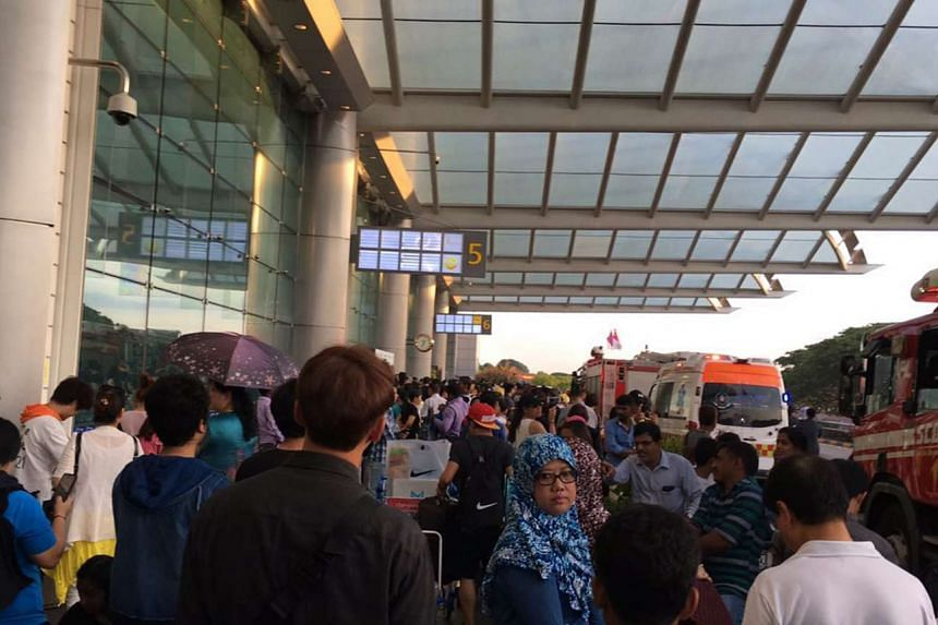 Passengers waiting outside Changi Airport Terminal 2 after being evacuated after a fire broke out on May 16, 2017.